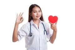 Jeune signe femelle asiatique d'OK d'exposition de docteur avec le coeur rouge Photo libre de droits