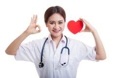 Jeune signe femelle asiatique d'OK d'exposition de docteur avec le coeur rouge Image libre de droits