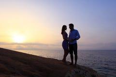 Jeune silhouette de couples au lever de soleil Image libre de droits