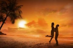 Jeune silhouette de couples sur une plage Image stock
