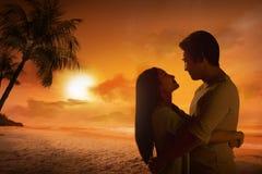 Jeune silhouette de couples sur une plage Photo libre de droits