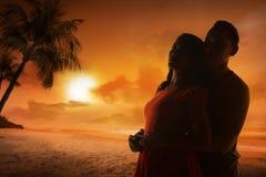 Jeune silhouette de couples sur une plage Photographie stock libre de droits