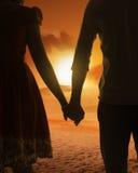 Jeune silhouette de couples sur une plage Photo stock