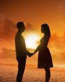 Jeune silhouette de couples sur une plage Photographie stock