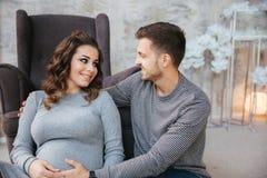 Jeune sist de famille près de la chaise et regard au ventre Femme de Pregman avec son homme aimé Couples heureux dans Noël image stock