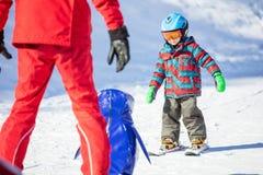 Jeune skieur glissant vers le bas vers vers l'Institut central des statistiques de pingouin et de ski de jouet Photo libre de droits