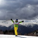Jeune skieur heureux avec des poteaux de ski dans des montagnes du soleil et le gra nuageux Photographie stock libre de droits