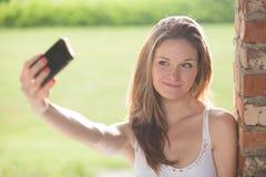 Jeune smartphone roux de selfie de femme extérieur Image stock