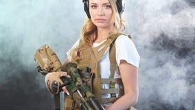 Jeune snipper femelle blond dans l'équipement militaire avec le fusil d'assaut dans le studio Mouvement lent banque de vidéos