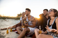 Jeune société des amis se réjouissant, se reposant à la plage pendant le lever de soleil Images stock