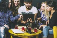 Jeune société gaie des amis avec le mobile, le comprimé et le thé Co Images stock