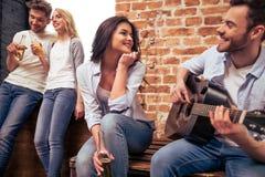 Jeune société jouant la guitare Photo libre de droits