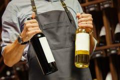 Jeune sommelier tenant la bouteille de vin rouge dans la cave photographie stock libre de droits