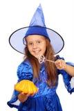 Jeune sorcière avec une baguette magique et un potiron magiques Image libre de droits