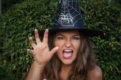 Jeune sorcière dans le chapeau noir effrayant avec sa main Photographie stock libre de droits