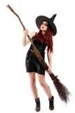 Jeune sorcière heureuse avec un balai, d'isolement sur le backgro blanc de studio Photographie stock libre de droits