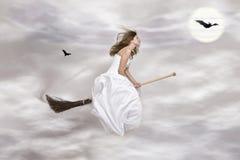Jeune sorcière sur le balai Photographie stock libre de droits