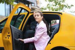 Jeune sortir de femme d'affaires du taxi Photo libre de droits