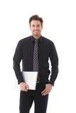 Jeune sourire d'ordinateur portatif de fixation d'homme d'affaires Image stock