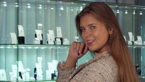 Jeune sourire femelle de client, choisissant des bijoux à vendre au magasin de luxe images libres de droits