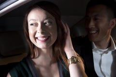 Jeune sourire, heureux, couples se reposant dans leur voiture et arrivant à un événement de tapis rouge la nuit dans Pékin Image stock
