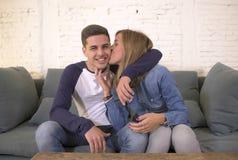 Jeune sourire heureux et romantique attrayant de divan d'offre de caresse d'ami et d'amie de couples à la maison espiègle dans le Image stock