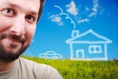 Jeune sourire mâle sur le pré vert avec h abstrait Image stock