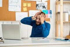 Jeune sourire réussi étonné d'homme d'affaires, se reposant sur le lieu de travail avec l'ordinateur portable Fond de bureau Photos stock