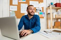 Jeune sourire réussi d'homme d'affaires, se reposant sur le lieu de travail avec l'ordinateur portable Fond de bureau Photographie stock libre de droits