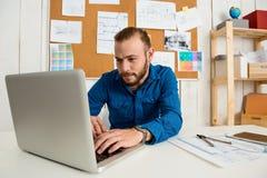 Jeune sourire réussi d'homme d'affaires, se reposant sur le lieu de travail dactylographiant sur l'ordinateur portable Fond de bu Photographie stock