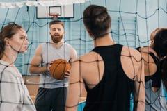 Jeune sportif avec la boule parlant avec des équipiers dans la salle de gymnastique Images libres de droits