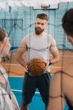 Jeune sportif avec la boule parlant avec des équipiers dans la salle de gymnastique Photo libre de droits