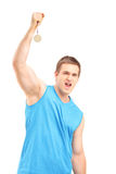 Jeune sportif euphorique tenant une médaille d'or Photographie stock libre de droits