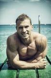 Jeune, sportif homme beau de muscle sur le pilier Image libre de droits