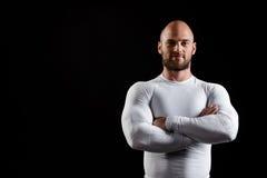 Jeune sportif puissant dans l'habillement blanc au-dessus du fond noir photos libres de droits