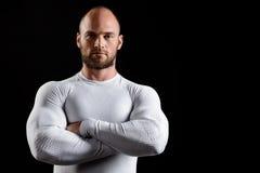 Jeune sportif puissant dans l'habillement blanc au-dessus du fond noir photographie stock