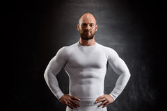 Jeune sportif puissant dans l'habillement blanc au-dessus du fond noir photos stock