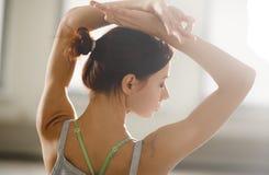Jeune sportive décontractée faisant le yoga et méditant dans le studio Image libre de droits