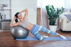 Jeune sportive faisant des exercices avec la boule sur un tapis à la maison Image stock