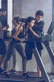 Jeune sportive sportive courant sur le tapis roulant au gymnase Photographie stock