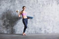 Jeune sportive tenant le tapis de yoga à l'intérieur photographie stock