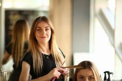 Jeune styliste en coiffure faisant des boucles pour la cliente de fille photos stock