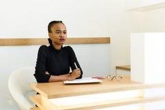 Jeune stylo de participation noir sûr de femme d'affaires et pensée au bureau dans le bureau photographie stock
