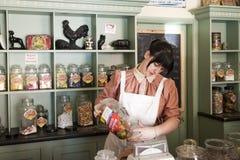 Jeune sucrerie femelle de portion d'employé de magasin Photo stock