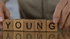 Jeune, supérieur homme faisant le mot des cubes en bois, souvenirs, désir d'être plus jeune clips vidéos