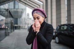 Jeune support Arabe en difficulté de femme dehors Elle éternue dans la serviette blanche Le modèle porte les vêtements noirs et l image libre de droits