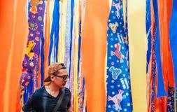 Jeune support asiatique d'homme avec le fond vibrant coloré de tissu image stock
