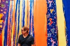 Jeune support asiatique d'homme avec le fond vibrant coloré de tissu photos stock