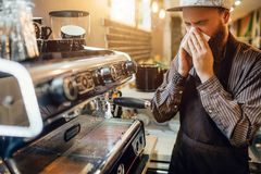 Jeune support barbu en difficulté de batista à la machine de café et éternuement dans la serviette blanche Il est seul dans la cu image stock