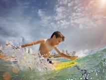 Jeune surfer, jeune garçon heureux dans l'océan sur la planche de surf photos stock